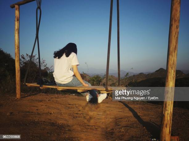 rear view of woman sitting on swing against clear blue sky - son la stock pictures, royalty-free photos & images