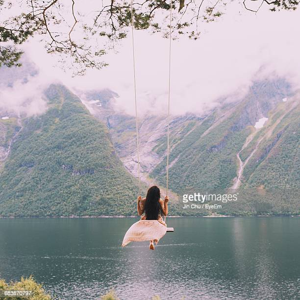 Rear View Of Woman Sitting On Swing By Lake Against Mountain