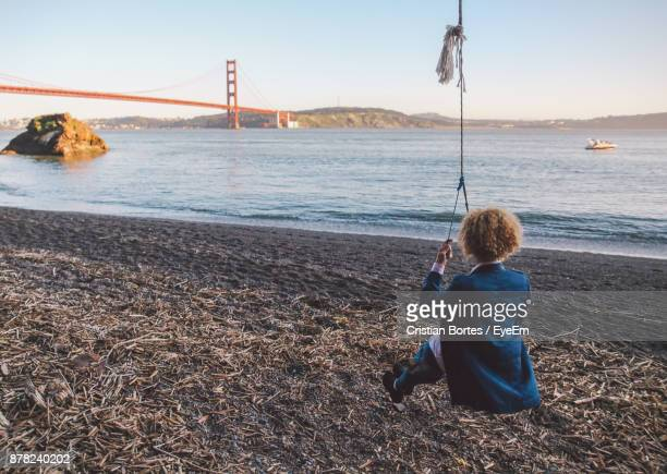 Rear View Of Woman Sitting On Swing With Golden Gate Bridge In Background