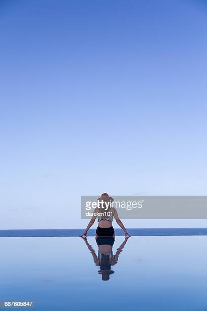 Rear view of Woman sitting on the edge of an infinity swimming pool