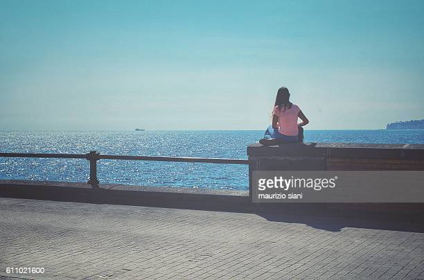 rear view of woman sitting rear view of woman sitting - one young woman only stock pictures, royalty-free photos & images