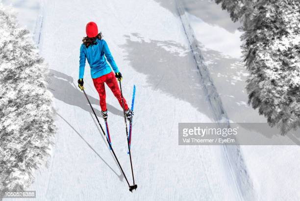rear view of woman skiing on snow - winter sport stock pictures, royalty-free photos & images