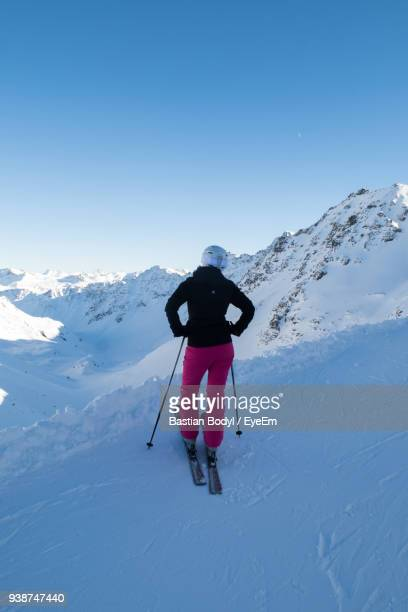 Rear View Of Woman Skiing On Snowcapped Mountain Against Sky