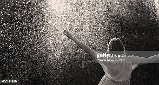 rear view of woman spraying water - paulien tabak stock pictures, royalty-free photos & images