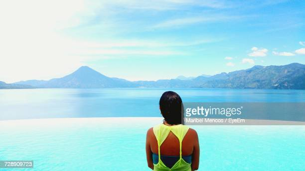 rear view of woman standing against blue sea and sky - guatemala city stock pictures, royalty-free photos & images