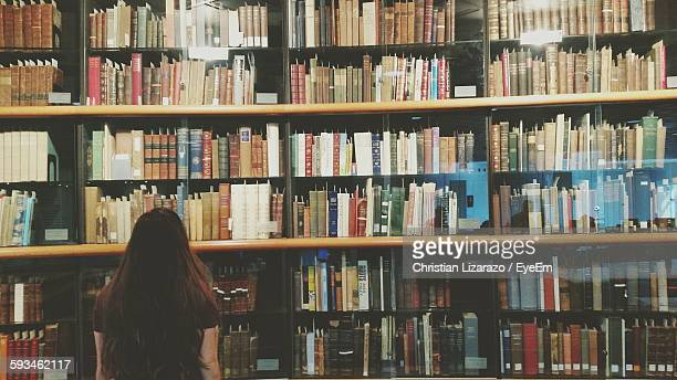 Rear View Of Woman Standing Against Bookshelf In Library