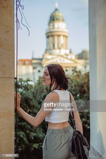 rear view of woman standing against concert hall - konzerthaus berlin stock pictures, royalty-free photos & images