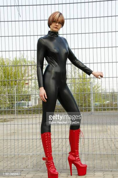rear view of woman standing against fence - latex photos et images de collection