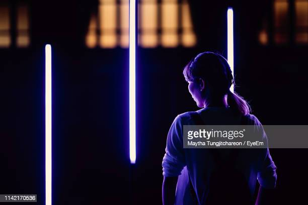 rear view of woman standing against illuminated lights at night - illuminated stock pictures, royalty-free photos & images