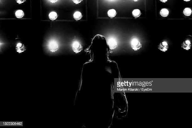 rear view of woman standing against illuminated lights at night - catwalk stock pictures, royalty-free photos & images