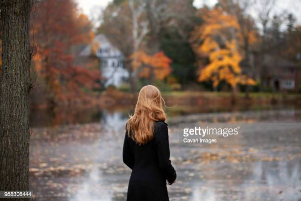 rear view of woman standing against lake - overcoat stock pictures, royalty-free photos & images