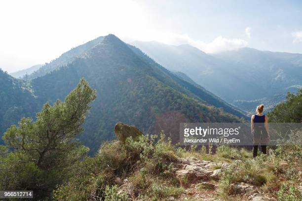 rear view of woman standing against mountains - liguria foto e immagini stock