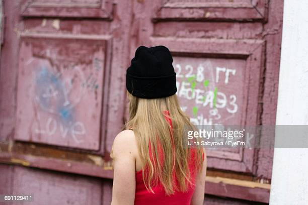 Rear View Of Woman Standing Against Old Door