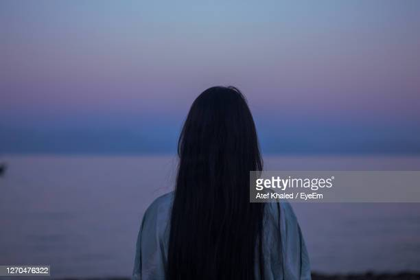 rear view of woman standing against sea at sunset - egypt stock pictures, royalty-free photos & images
