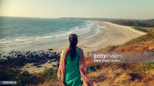 rear view of woman standing against sea - salwar kameez stock pictures, royalty-free photos & images