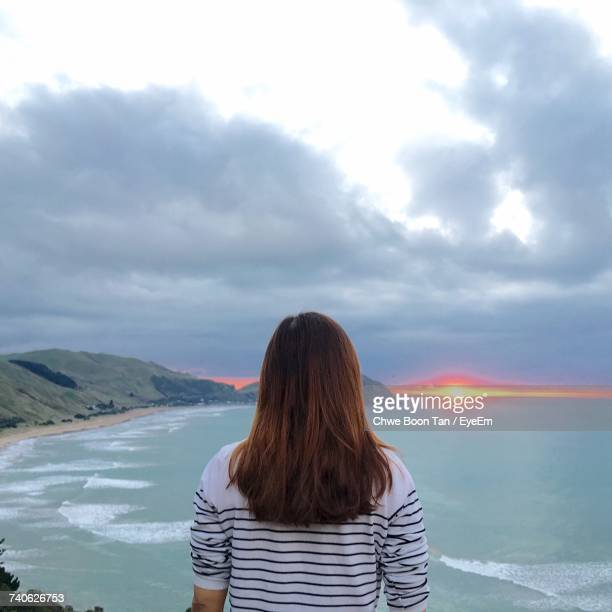 rear view of woman standing against sky - gisborne stock photos and pictures