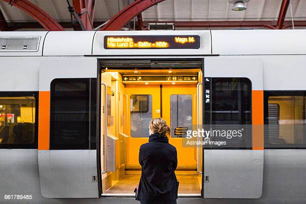 rear view of woman standing against train at railroad station - vehicle door stock pictures, royalty-free photos & images