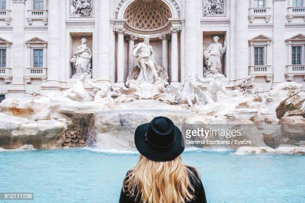 rear view of woman standing against trevi fountain - rome italy stock pictures, royalty-free photos & images