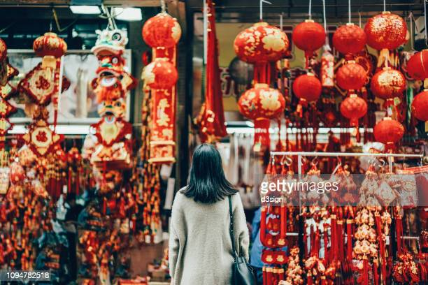 rear view of woman standing against various chinese new year decorations and ornaments on city street - chinese new year stock pictures, royalty-free photos & images