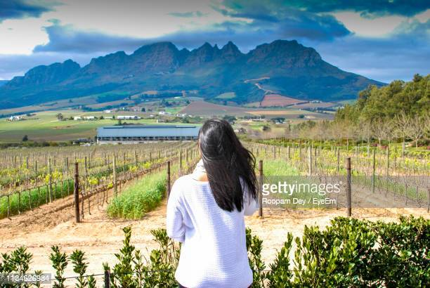 Rear View Of Woman Standing Against Vineyard