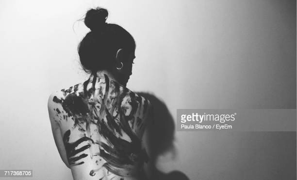 rear view of woman standing against wall - violenza foto e immagini stock
