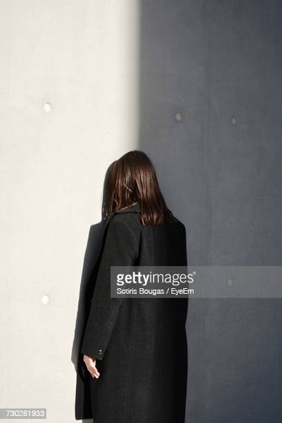 rear view of woman standing against wall - trench coat stock pictures, royalty-free photos & images