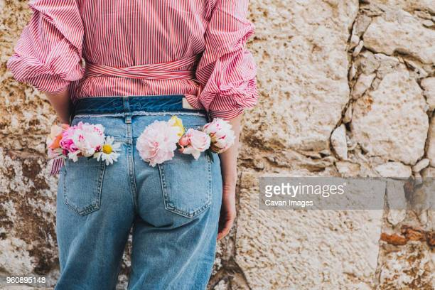 Rear view of woman standing against wall with flowers in back pocket
