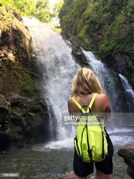 rear view of woman standing against waterfall at forest - hannah brooks stock pictures, royalty-free photos & images