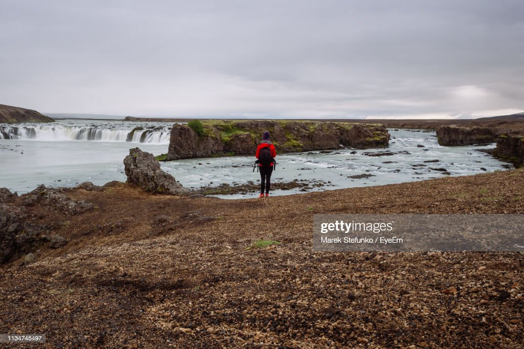 Rear View Of Woman Standing Against Waterfall : Stock Photo