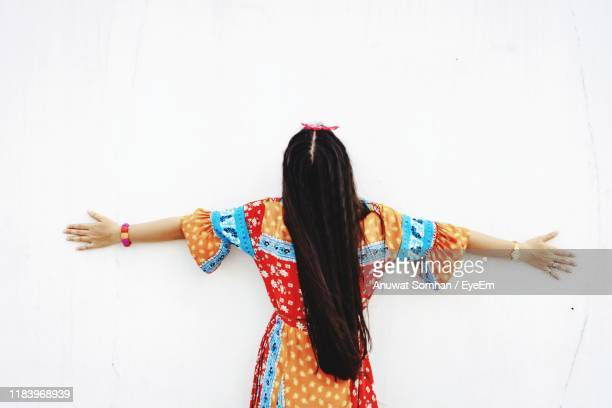 rear view of woman standing against white background - anuwat somhan stock photos and pictures