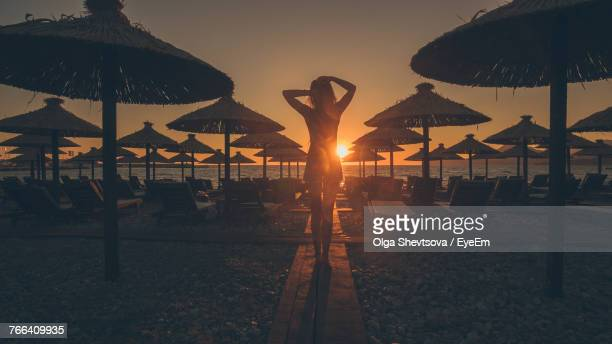 Rear View Of Woman Standing Amidst Parasols At Beach