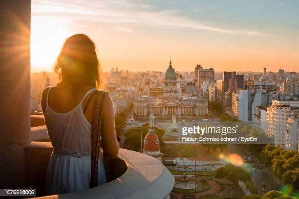 rear view of woman standing at balcony against cityscape during sunset - travel fotografías e imágenes de stock