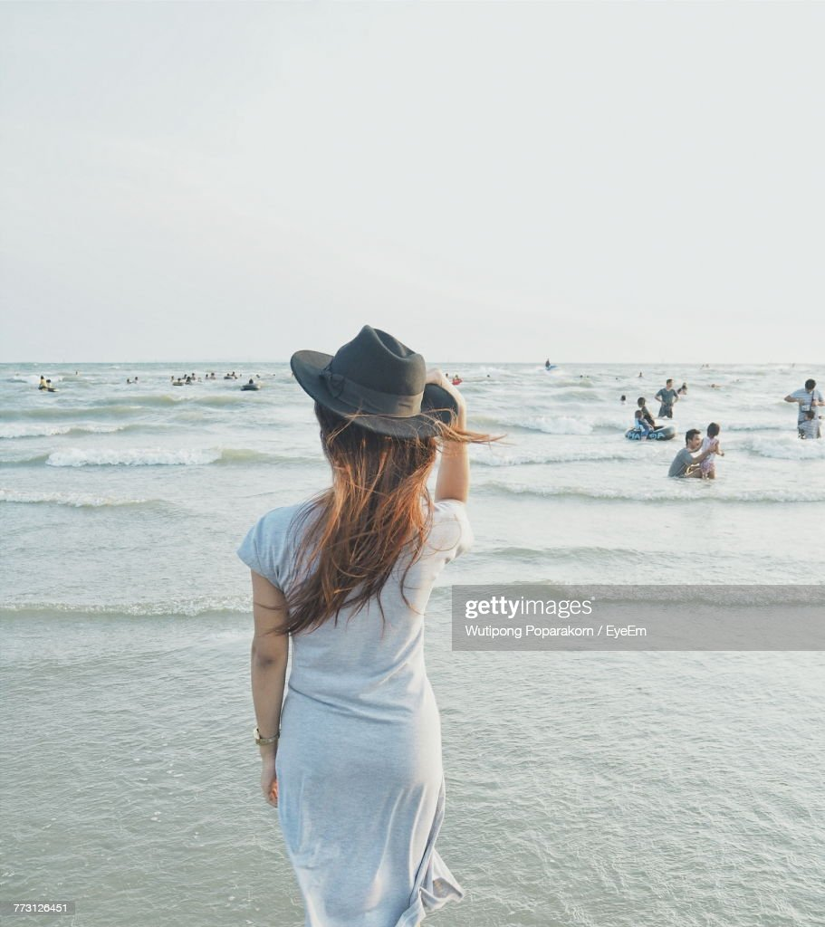 Rear View Of Woman Standing At Beach Against Clear Sky : Stock Photo