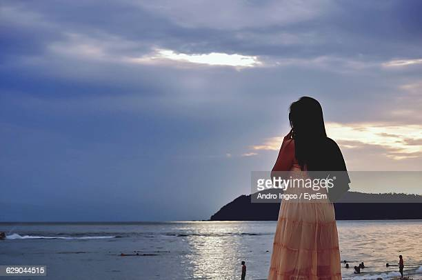 Rear View Of Woman Standing At Beach Against Cloudy Sky During Sunset