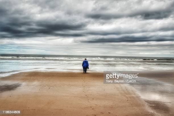 rear view of woman standing at beach against cloudy sky - saltburn stock pictures, royalty-free photos & images