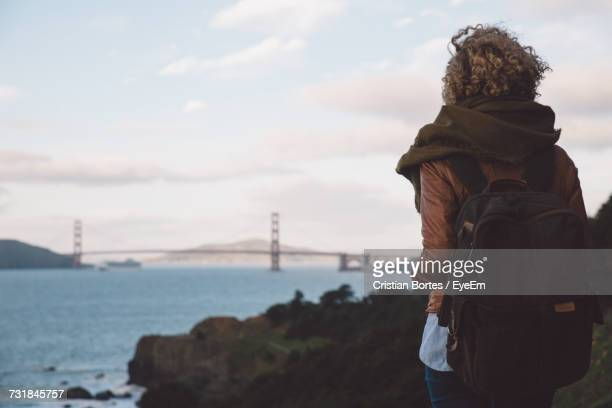 rear view of woman standing at beach against cloudy sky - bortes stock pictures, royalty-free photos & images