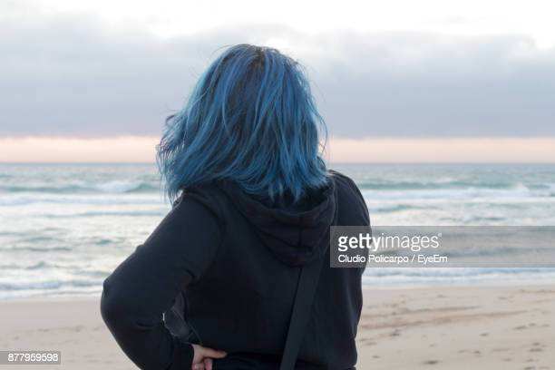Rear View Of Woman Standing At Beach Against Cloudy Sky
