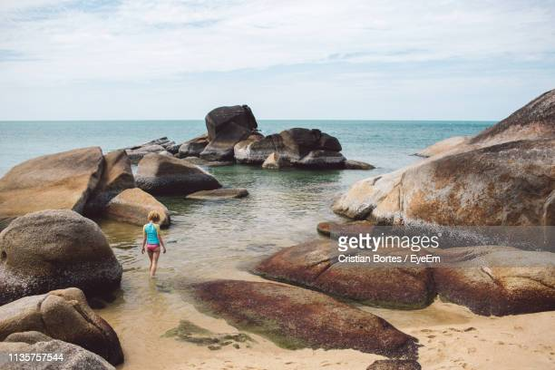 rear view of woman standing at beach against sky - bortes foto e immagini stock