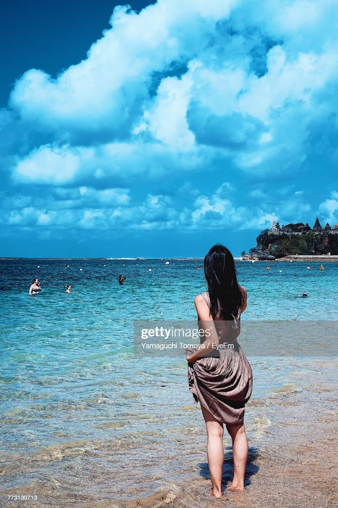 Rear View Of Woman Standing At Beach Against Sky : Stock-Foto
