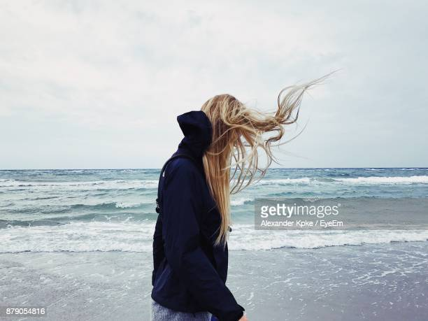 rear view of woman standing at beach against sky - blonde hair stock pictures, royalty-free photos & images