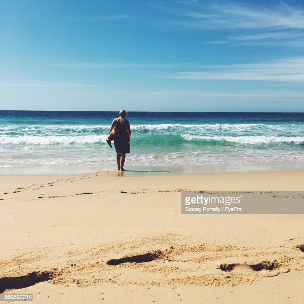rear view of woman standing at beach against sky - merimbula stock pictures, royalty-free photos & images