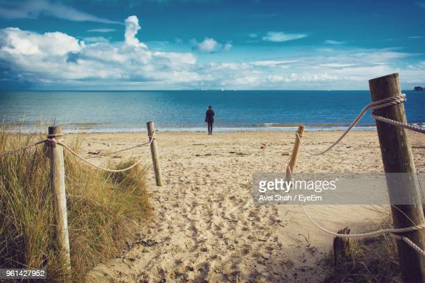 rear view of woman standing at beach against sky - bournemouth stock pictures, royalty-free photos & images