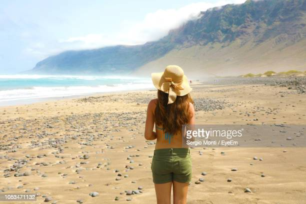 rear view of woman standing at beach - arrecife stock photos and pictures