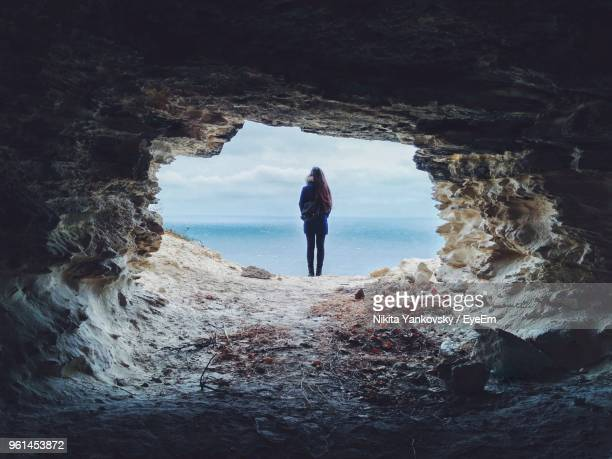 rear view of woman standing at cave entrance - light at the end of the tunnel stock pictures, royalty-free photos & images