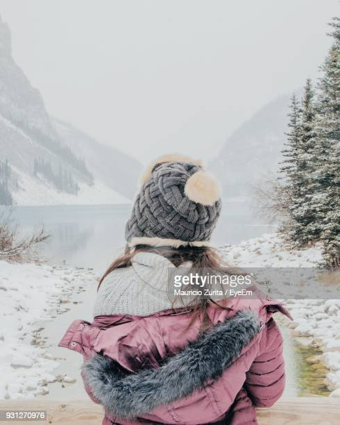 Rear View Of Woman Standing At Lake Against Sky During Winter