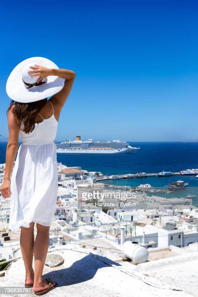 Rear View Of Woman Standing At Mykonos Beach Against Clear Blue Sky