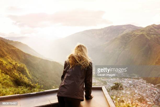 Rear view of woman standing at observation point against mountains and sky