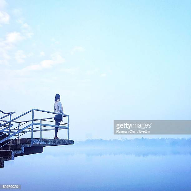Rear View Of Woman Standing At Observation Point Over Lake
