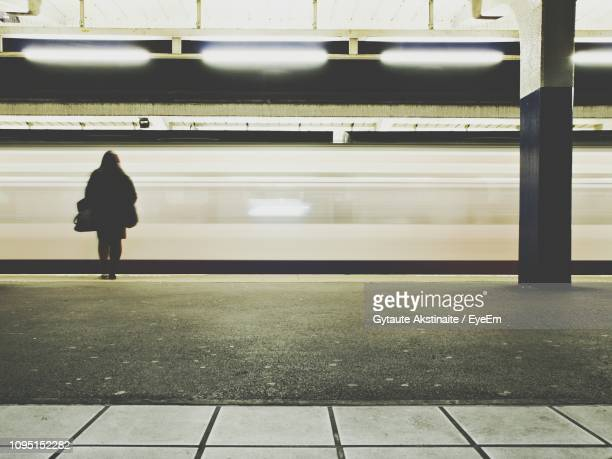 rear view of woman standing at railroad station - london underground stock pictures, royalty-free photos & images