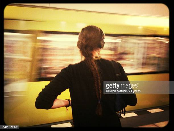 Rear View Of Woman Standing At Railroad Station